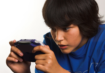 Boy obsessing with handheld video game